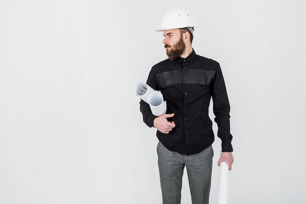 Bauingenieur, der plan in seiner hand gegen weißen hintergrund hält