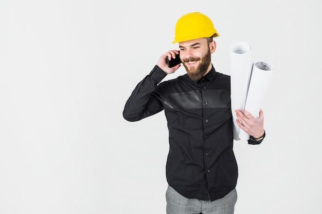 Bauingenieur, der plan in seiner hand spricht auf mobiltelefon hält