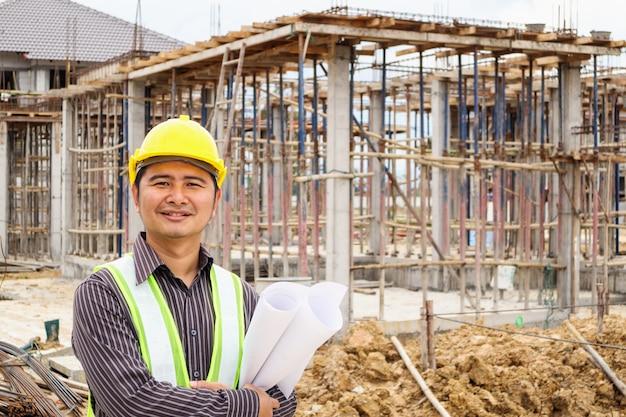Bauingenieur des asiatischen geschäftsmannes im schutzhelm und im blaupausenpapier zur hand auf hausbaustelle
