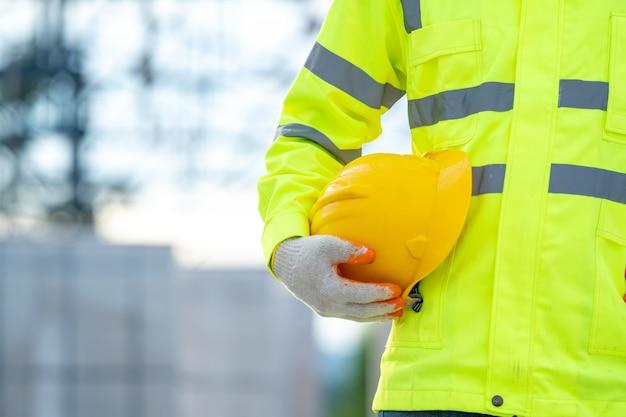 Bauingenieur hält gelben schutzhelm bei der arbeit auf der baustelle.