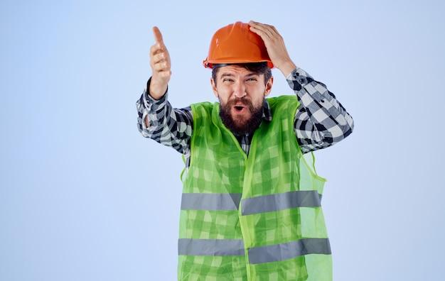 Bauingenieur im schutzhelm gestikuliert mit den händen auf der blauen und reflektierenden weste.