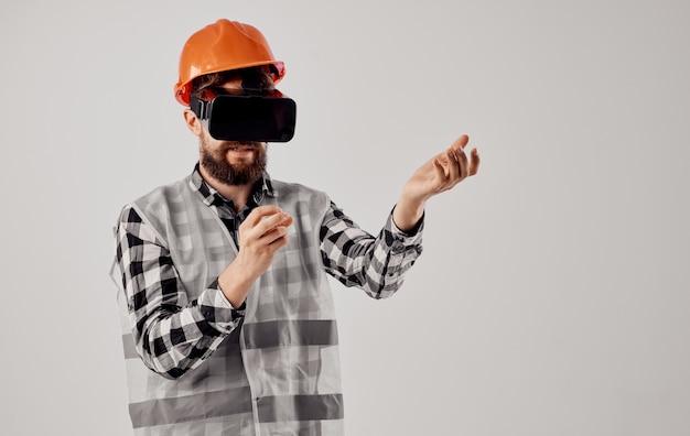 Bauingenieur in einem orangefarbenen helm und in der 3d-brille auf einem hellen hintergrund. hochwertiges foto