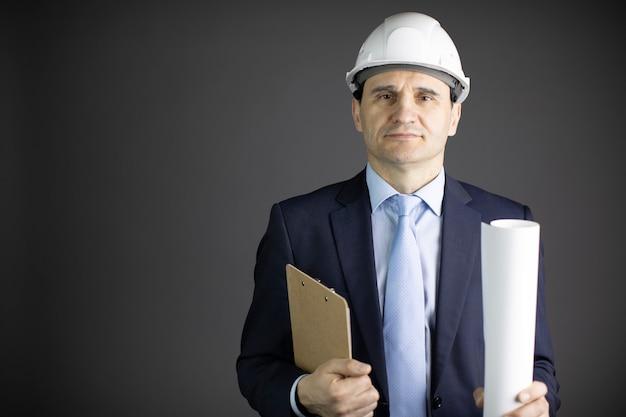 Bauingenieur in schutzhelm hält zwischenablage blaupausenrolle mit textraum