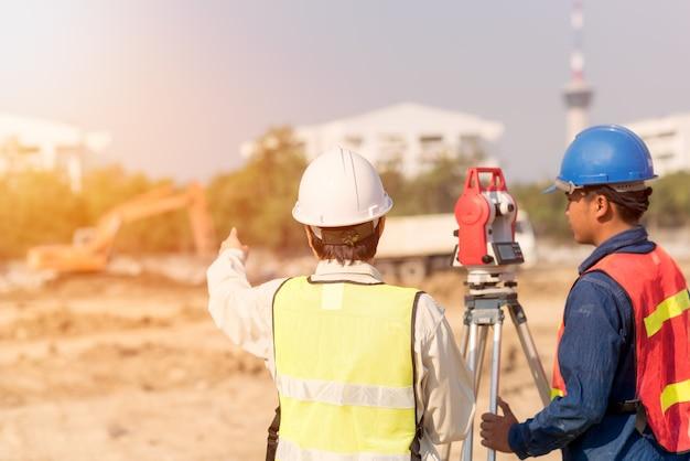 Bauingenieur mit der vorarbeiterarbeitskraft, die baustelle überprüft