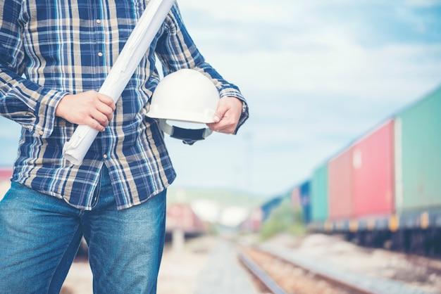 Bauingenieur-team mit bauplan für ein projekt vor ort im werk der eisenbahnschienenindustrie. industrietechnisches konzept.