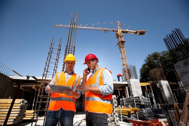 Bauingenieur und architekt in orangefarbenen arbeitswesten