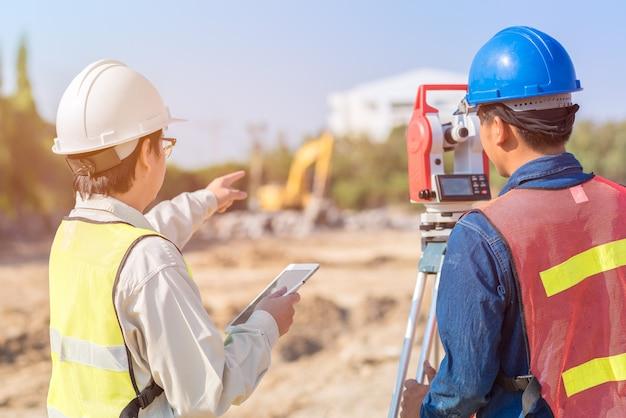 Bauingenieur- und vorarbeiterarbeitskraft, die baustelle überprüft