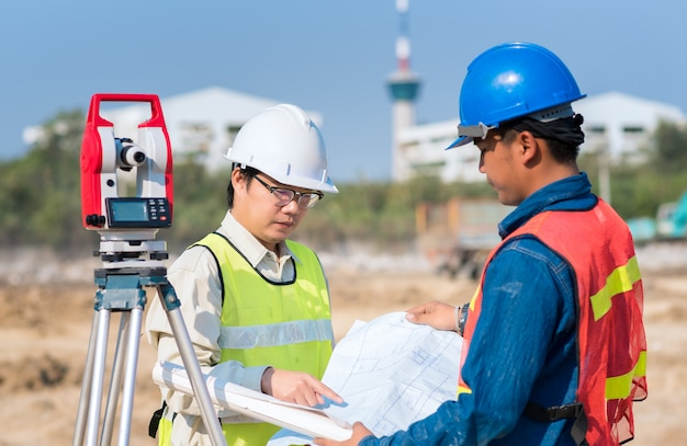 Bauingenieur- und vorarbeiterarbeitskraft, die bauzeichnung am standort auf neues infrastrukturbauprojekt überprüft