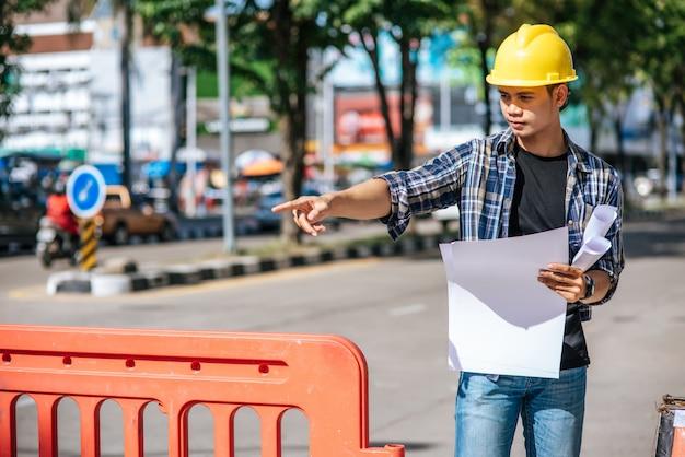 Bauingenieure arbeiten entsprechend den straßenverhältnissen und haben barrieren.