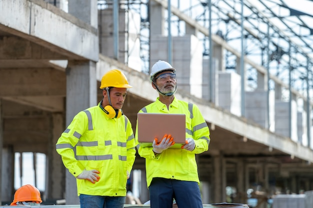 Bauingenieure arbeiten und prüfen neue projekte auf der baustelle.