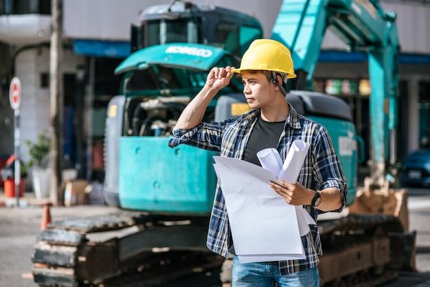 Bauingenieure arbeiten unter großen straßen- und maschinenbedingungen.