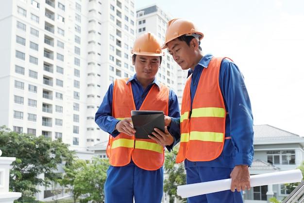 Bauingenieure, die daten bezüglich der tablette überprüfen
