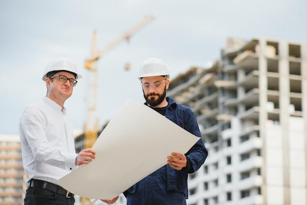 Bauingenieure mit einer skizze auf einer baustelle