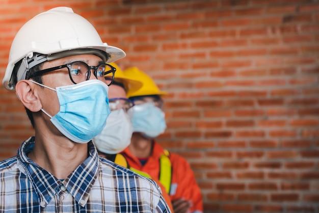 Bauingenieure und drei architekten tragen medizinische masken, um koronarinfektionen vorzubeugen. covid-19 - supervisor und follower tragen masken im baubereich.