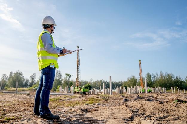 Bauingenieurinspektionsstapelarbeit an der infrastrukturbaustelle