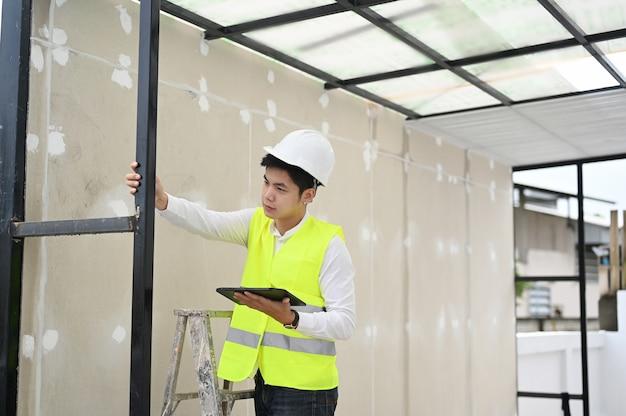 Bauinspektor, der mit dem hauptgebäude der digitalen tablet-checkliste arbeitet
