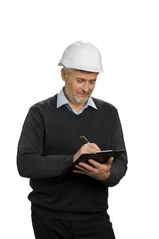 Bauinspektor prüft das objekt. reifer ingenieur, der in die zwischenablage schreibt