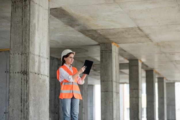 Baukonzept des ingenieurs oder architekten, der auf der baustelle arbeitet. eine frau mit einem tablet auf einer baustelle. büro für architektur.