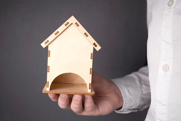 Baukonzepte. hand, die ein hölzernes miniaturhaus hält, hält die hand des mannes symbolisch ein mini-holzhaus