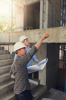 Baukonzepte, ingenieur und architekt, die an der baustelle mit plan arbeiten