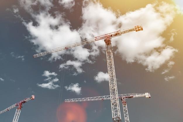 Baukräne arbeiten auf der baustelle vor blauem himmelshintergrund. ansicht von unten auf den industriekran. konzept des baus von mehrfamilienhäusern und renovierung von wohnungen. platz kopieren