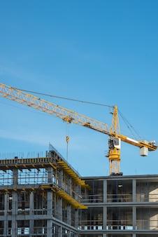 Baukran in der nähe eines neu gebauten hauses. aufbau und entwicklung eines vertikalen fotos