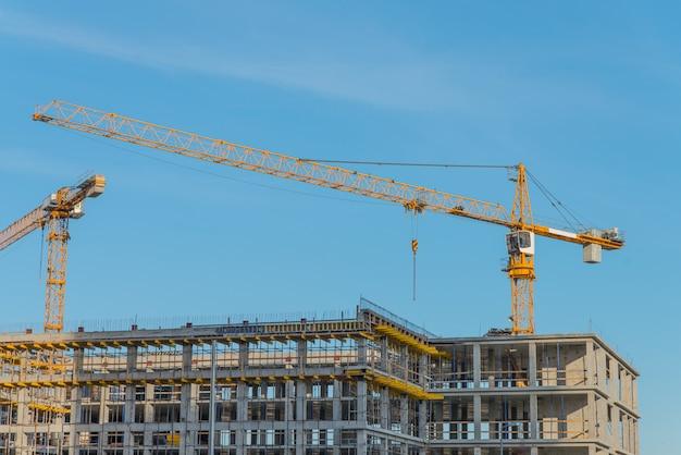 Baukran in der nähe eines neu gebauten hauses. konstruktions- und entwicklungskonzept
