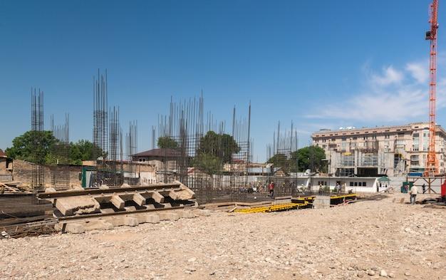 Baukran und eine konkrete struktur des gebäudes auf einem hintergrund der himmel