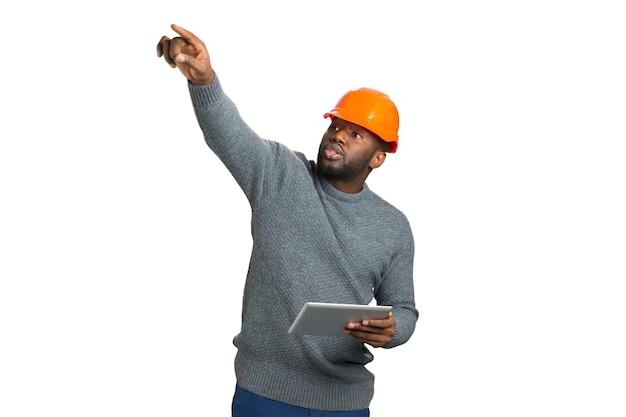 Bauleiter auf weißem hintergrund. junger architekt im orangefarbenen helm steuert bauprozess und zeigt mit dem finger nach oben