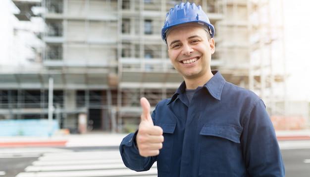 Bauleiter, der daumen vor einer baustelle aufgibt