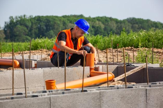 Bauleiter prüft das neue bungalowfundament des hauses, gebäudekonzept
