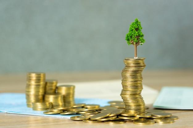 Baum, der auf stapel von goldenen münzen und von geschäftsbuch oder von kreditwarenkorb wächst