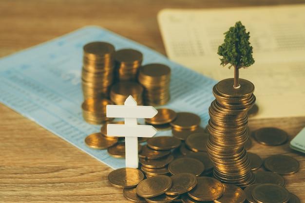 Baum, der auf stapel von goldenen münzen und von geschäftsbuch wächst