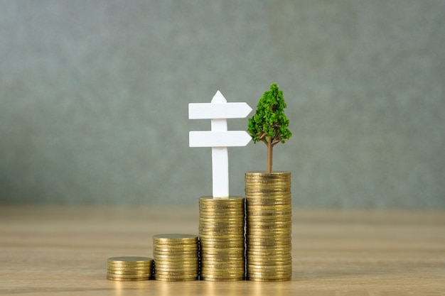 Baum, der auf stapel von goldenen münzen und von weißem zeichen des hölzernen brettes wächst