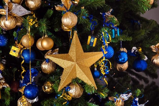 Baum geschmückt mit goldenen spielzeugen und bällen, weihnachten
