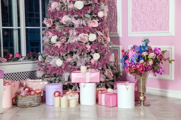 Baum in rosa spielzeug verziert. weihnachten mit geschenken im zimmerinnenraum