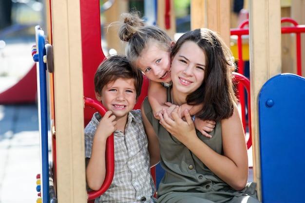 Baum verschiedene gealterte kinder, die auf spielplatz aufwerfen.