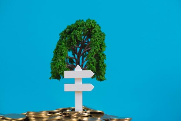 Baum wächst auf haufen von goldenen münzen und weißen holzbrett zeichen,