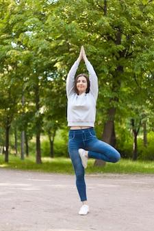Baum yoga pose auf park gasse