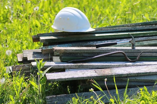 Baumaterial liegt auf grashammer und helm