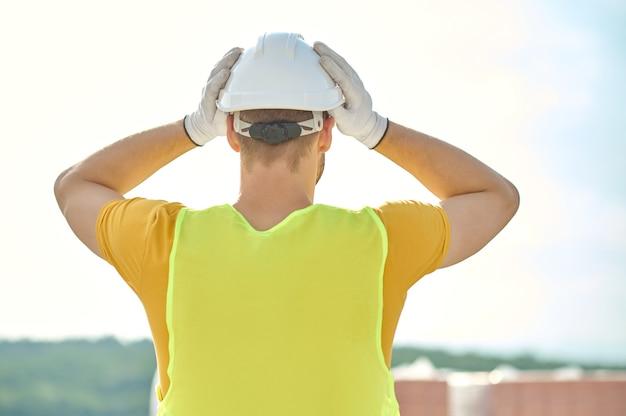 Baumeister bedeckt seinen kopf mit einem schutzhelm vor der arbeit