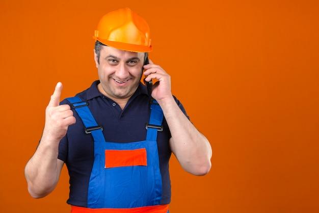 Baumeister, der bauuniform und sicherheitshelm mit lächeln auf gesicht zeigt, zeigt finger nach oben und spricht auf handy über isolierte orange wand