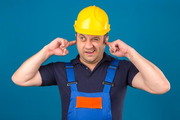 Baumeister, der bauuniform und sicherheitshelm trägt, der ohren wegen des lärms über isolierter blauer wand schließt