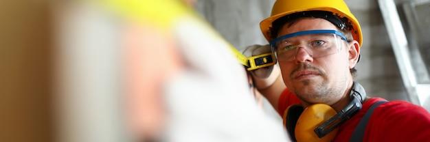 Baumeister, der die wandhöhe mit rouletteband misst