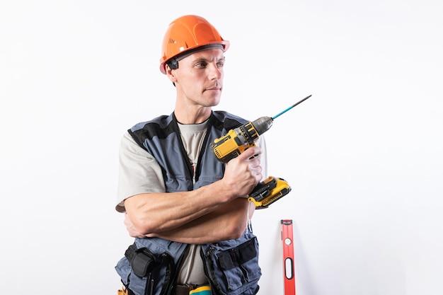 Baumeister, der einen bohrer wie eine waffe hält. in helm und arbeitskleidung. für jeden zweck.
