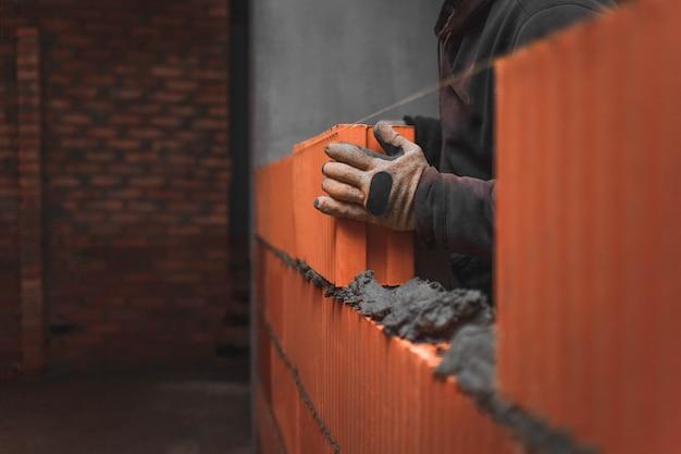 Baumeister, der einen großen ziegelsteinblock auf den mörtel legt, der eine wand schafft