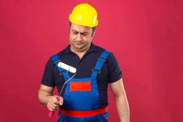 Baumeister, der konstruktionsuniform und sicherheitshelm trägt, die mit farbroller stehen, der skeptisch zweifelhaft über isolierter rosa wand fühlt
