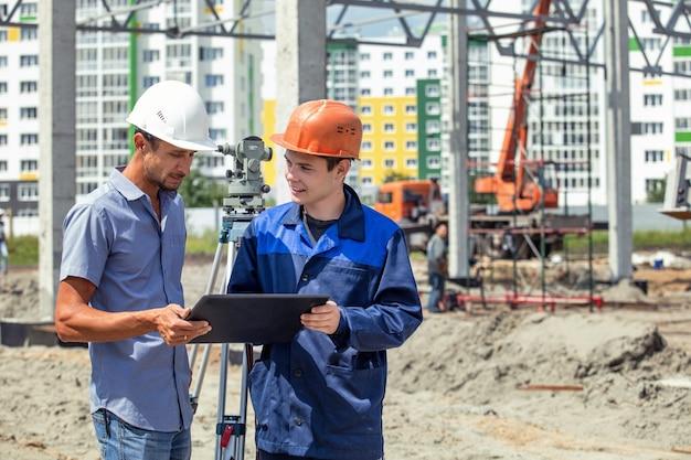 Baumeister gibt aufträge an arbeiter und bauherren, die auf der baustelle ein gebäude bauen