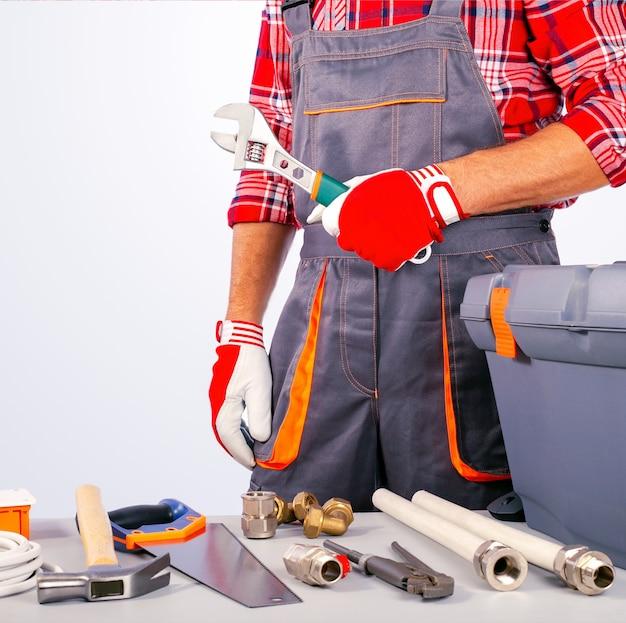 Baumeister, handwerker mit verstellbarem schraubenschlüssel und werkzeugkasten, instrumente auf dem tisch.