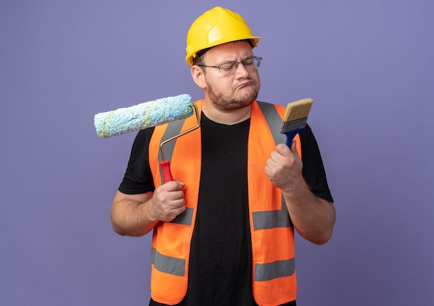 Baumeister in bauweste und schutzhelm, der farbroller und pinsel hält, der verwirrt aussieht und versucht, die wahl auf blauem hintergrund zu treffen